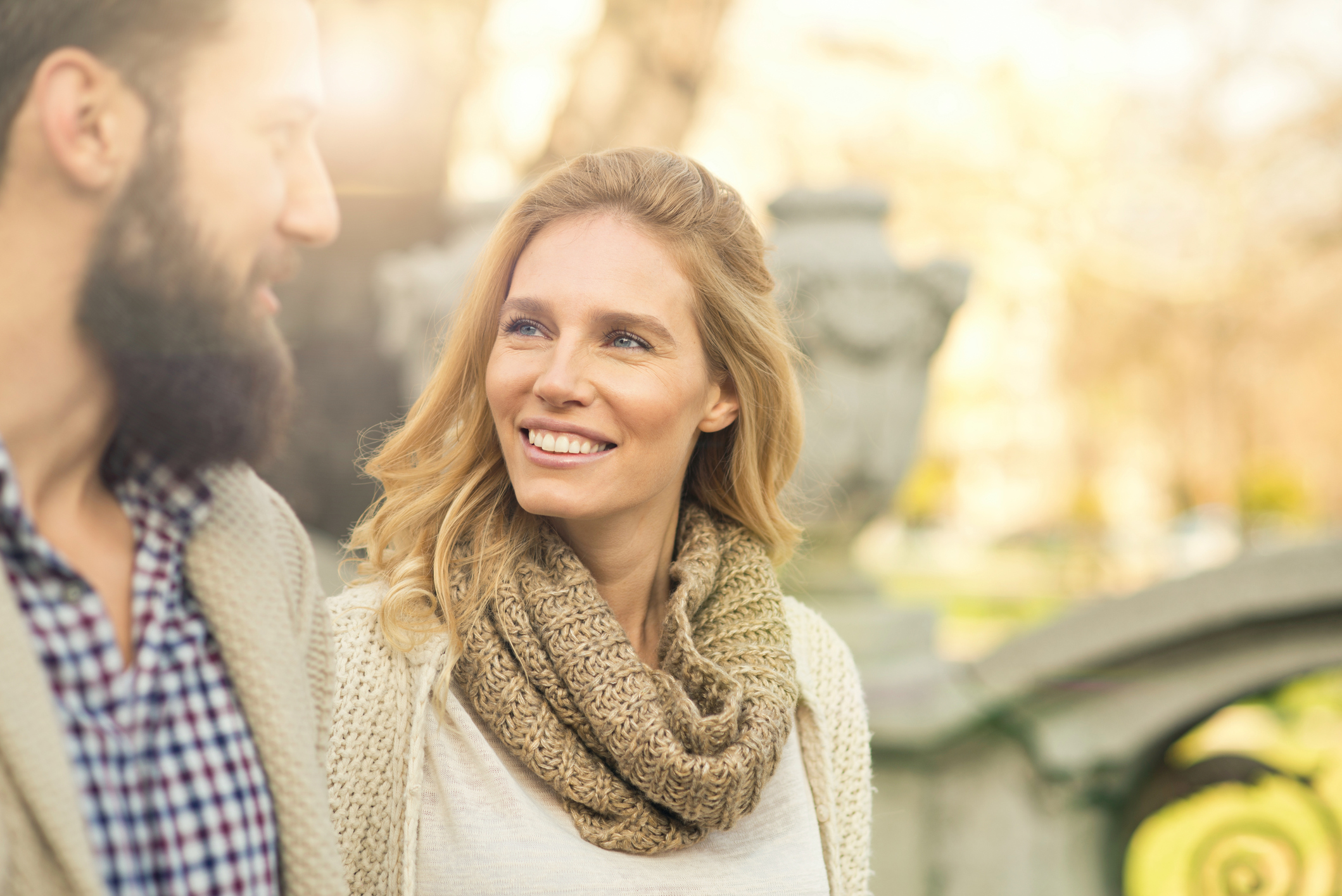 Woman with white teeth and a beautiful smile looking at man with a beard